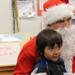 Santa Claus awaits for his elves to deliver presents to students from Albion Street.