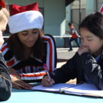 Senior Briana Perez helps a student with her homework during recess.