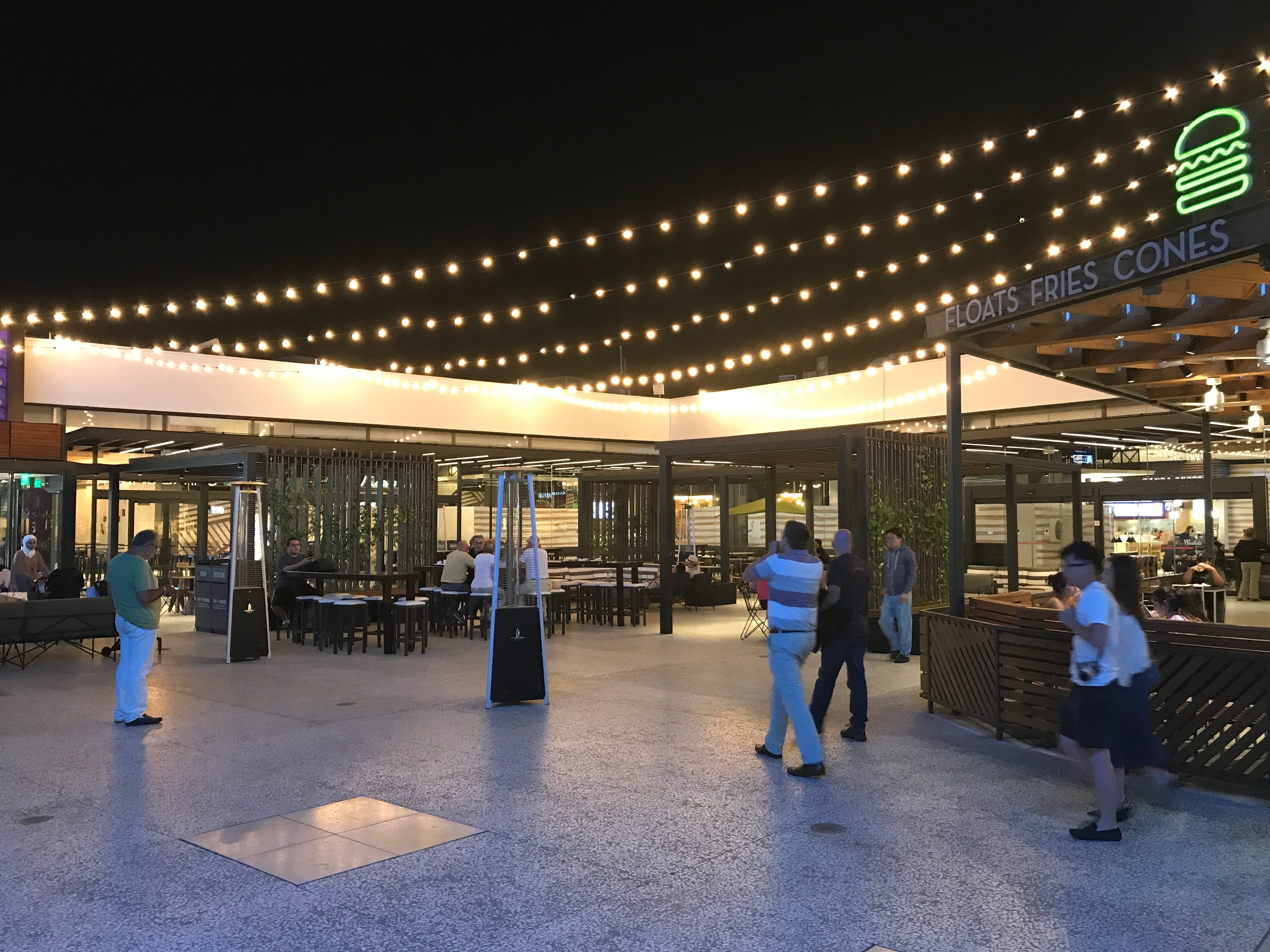 Customers mingle under the lights of the refurbished food court patio.